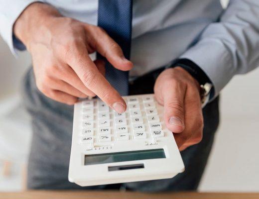 Homem usando uma calculadora.