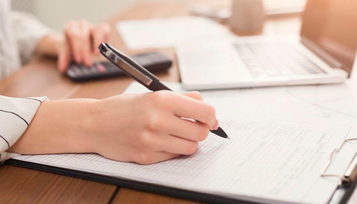Uma pessoa assinando alguma coisa em um papel, ela também está usando uma calculadora.