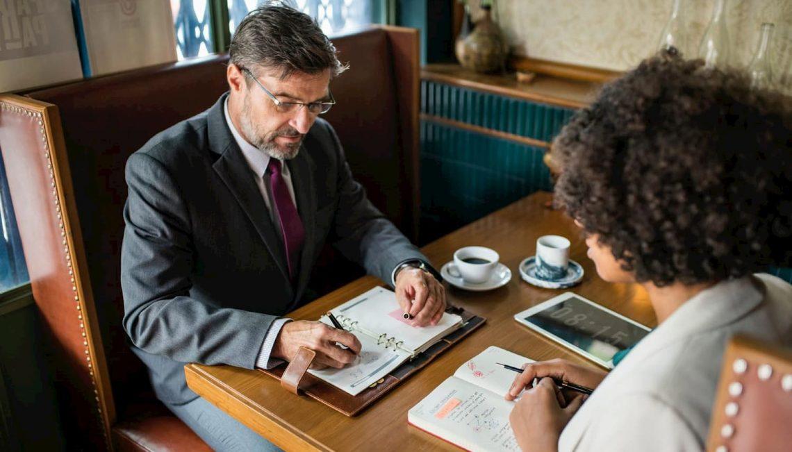 Dois empresários, um homem e uma mulher discutindo sobre o marketing jurídico.