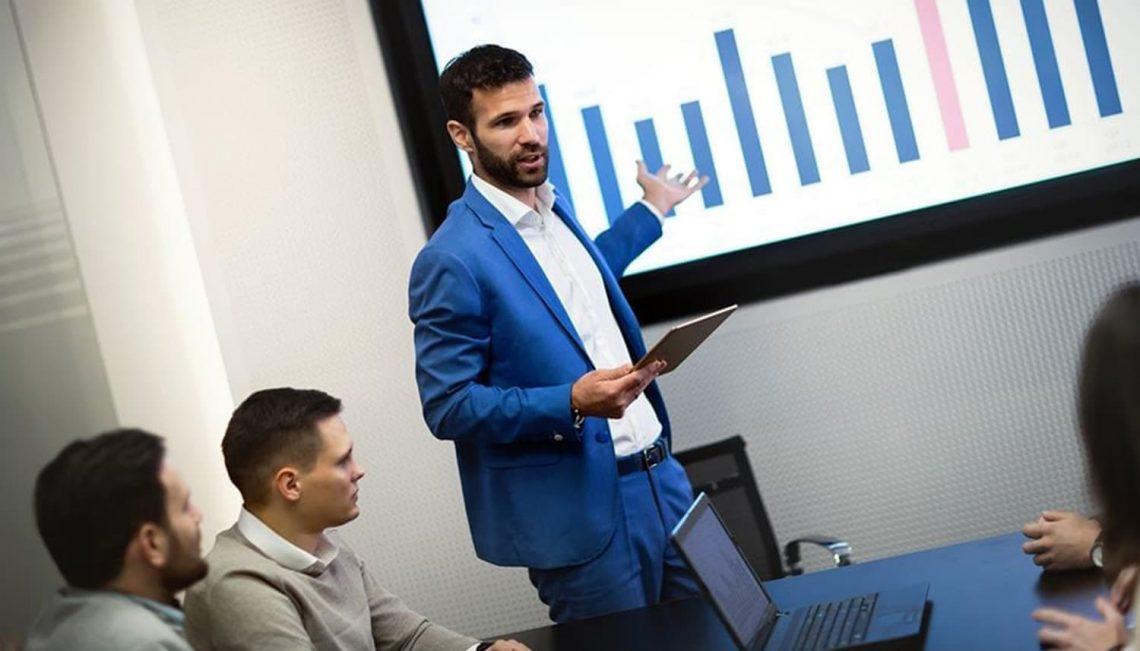 Homem empresário em frente a um grupo de pessoas, mostrando um gráfico.