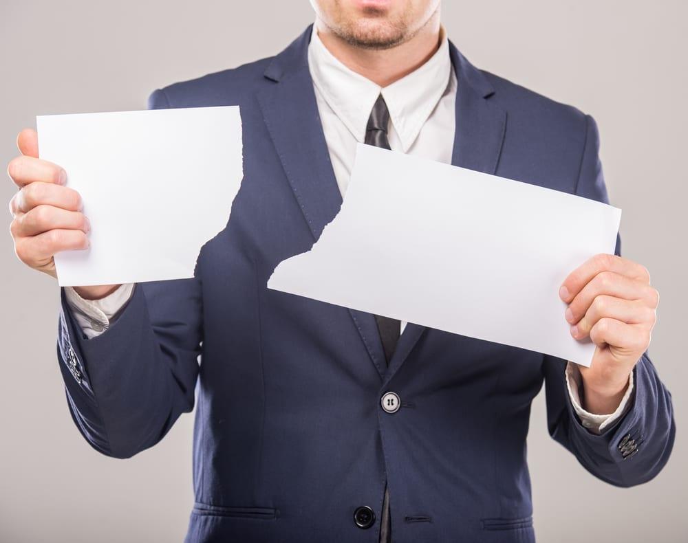 Empresario rasgando uma folha de papel.