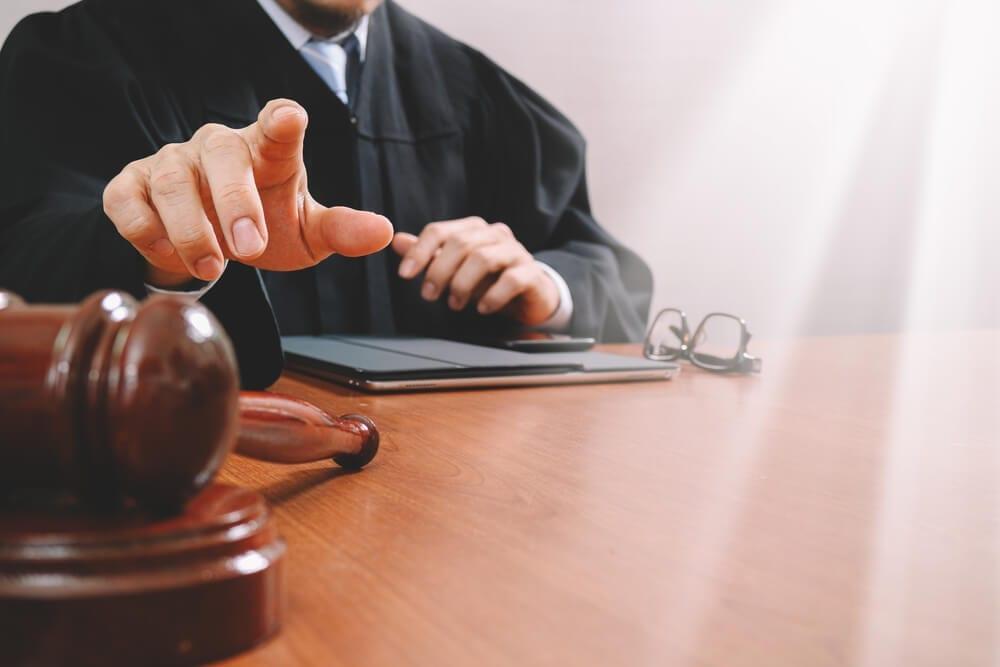 Imagem de um juiz movendo sua mão para pegar seu martelo.