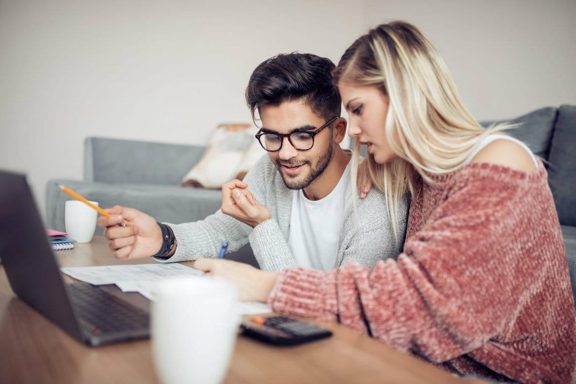 Um casal olhando para a tela do notebook comprando produtos para importaçãi