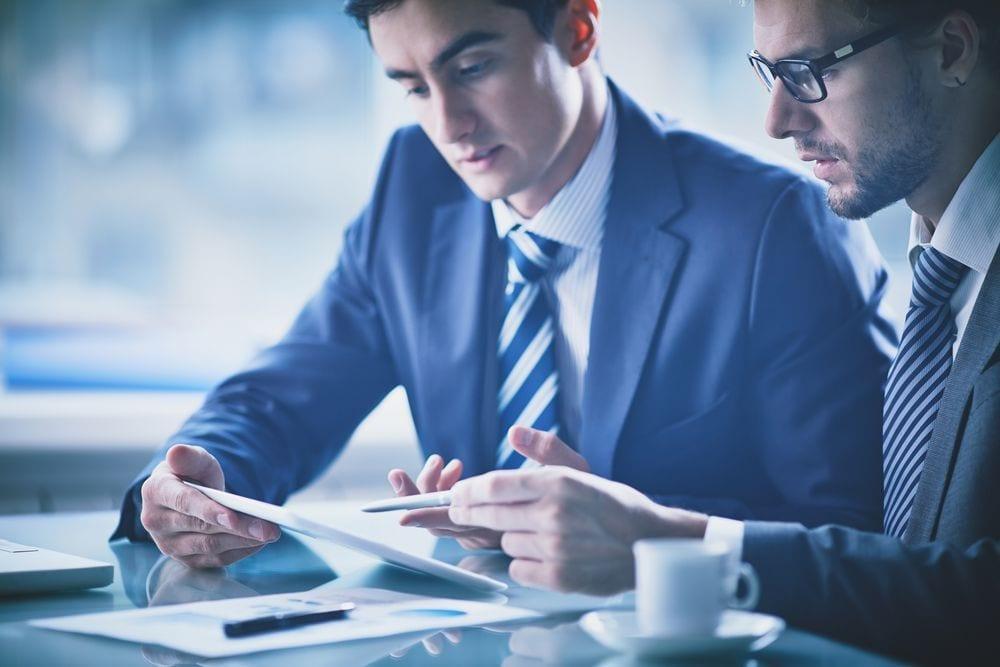 Duas pessoas conversando, enquanto olham um papel.