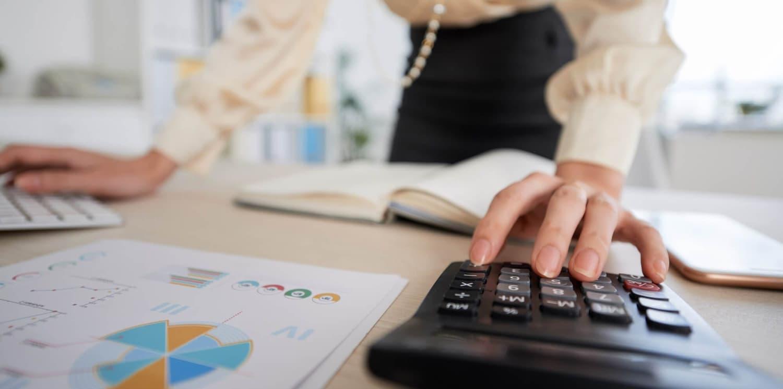 Mulher empresaria usando um calculadora em seu negócio de sucesso