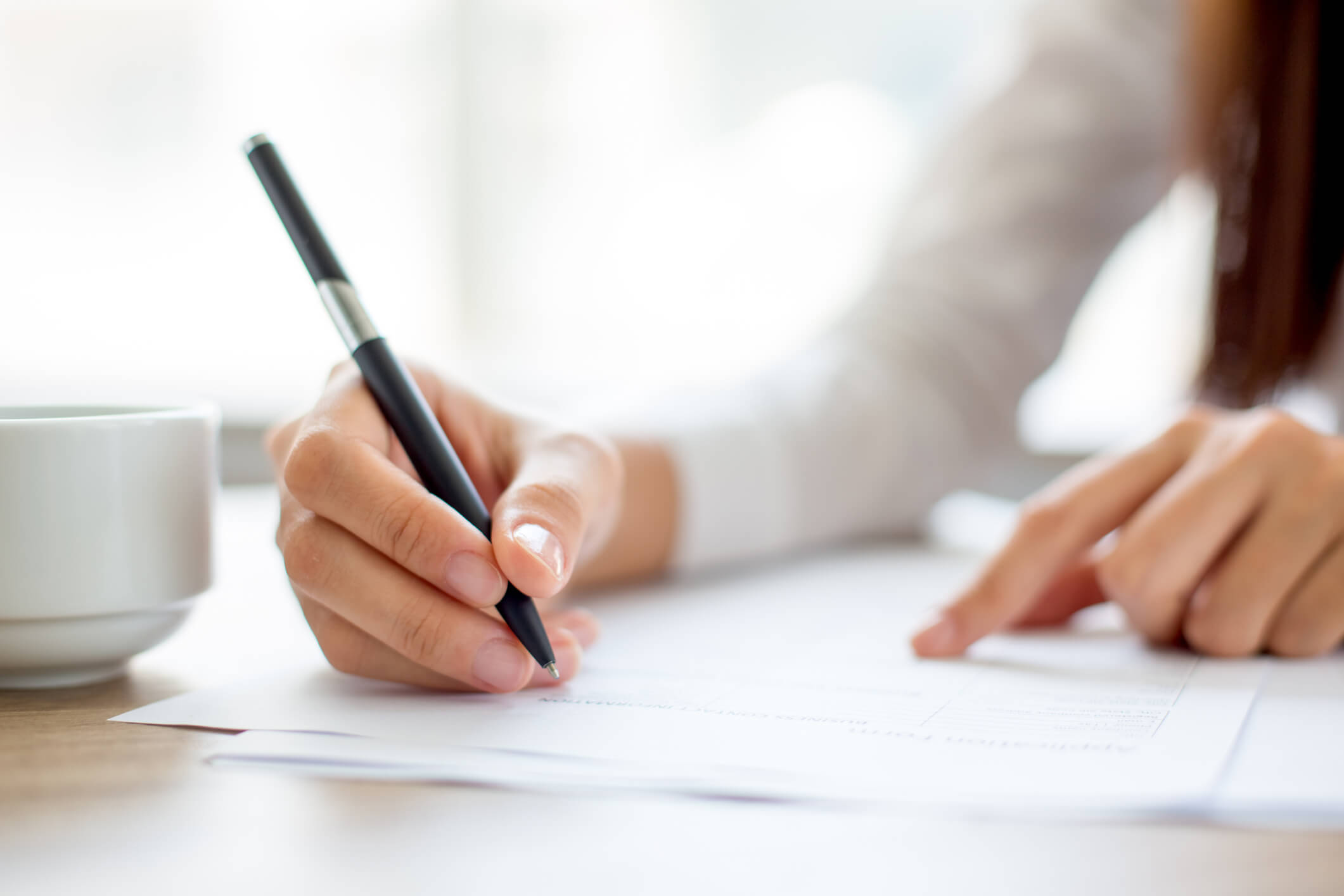 Mulher escrevendo em uma folha em cima de uma mesa.