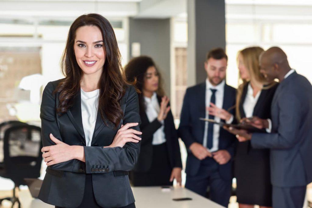Mulher empresária em frente aos seus funcionários