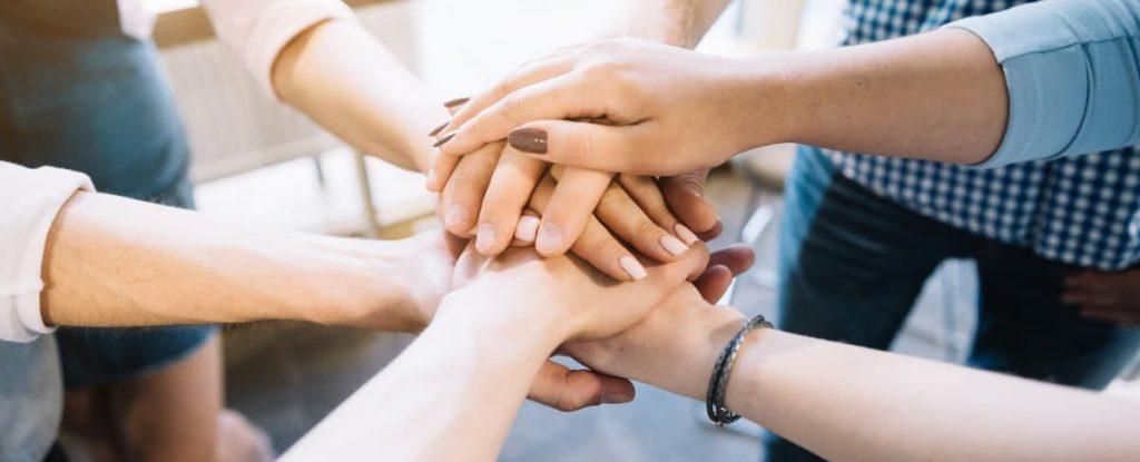 Várias pessoas com as mãos uma em cima da outra