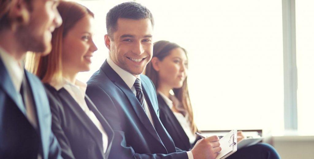 Reunião de negócios onde uma pessoa olha para câmera e sorri