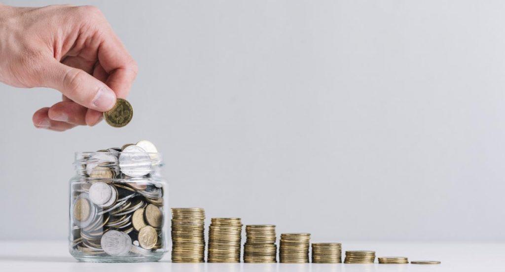 Pessoa colocando moedas em um pote de vidro