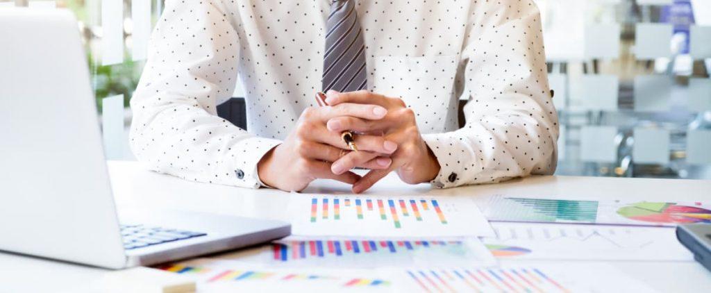Homem sentado em frente a uma mesa com uma caneta em sua mãos parece estar pensativo.