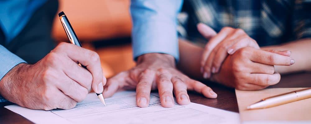 Duas pessoas em uma mesa uma está assinando um contrato.