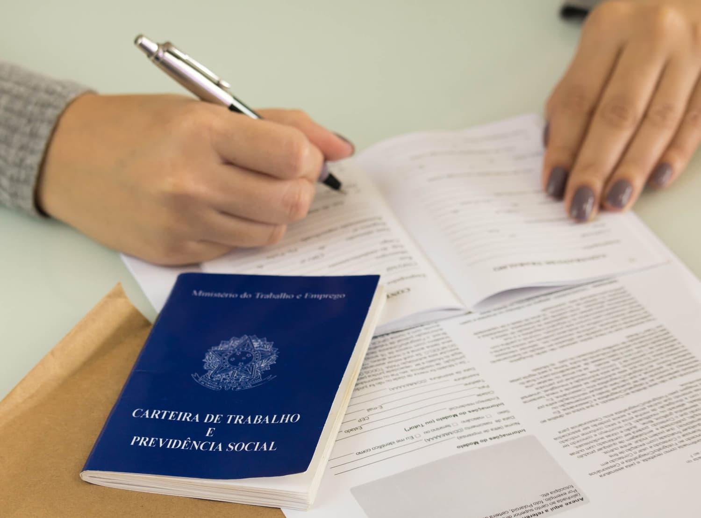 Pessoa assinando um documento sobre as férias trabalhistas. Com uma carteira de trabalho em cima da mesa.