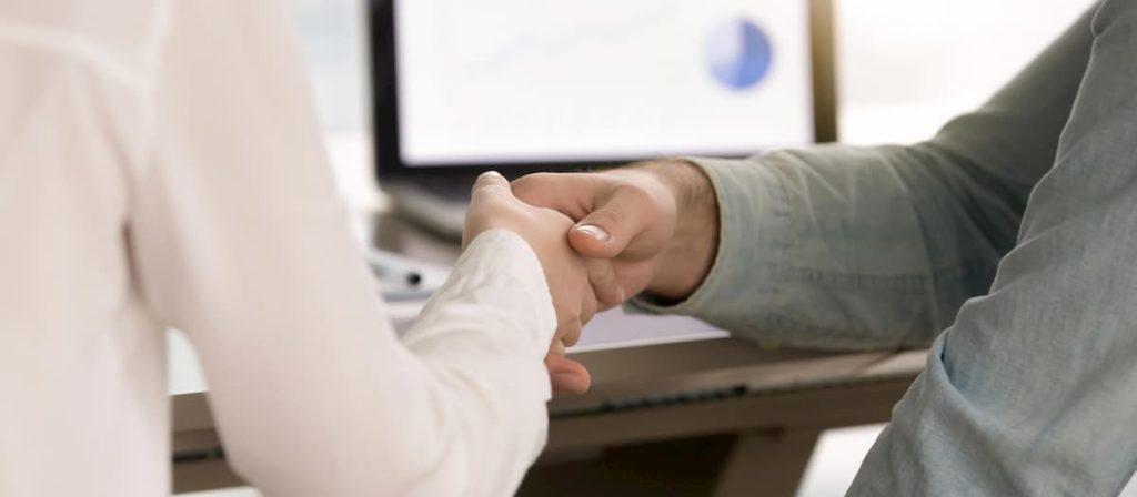 Dois empresários apertando as mãos, fechando um negócio.