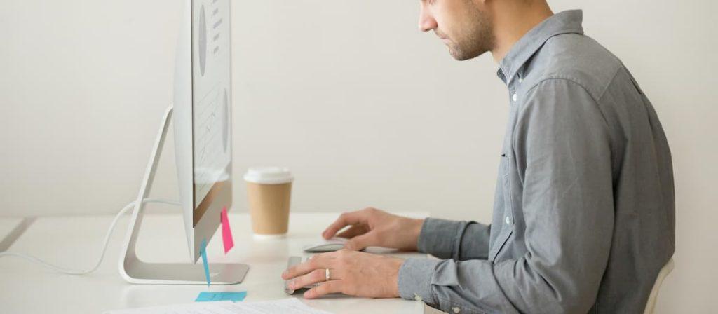 Homem sentado em frente a um computador.