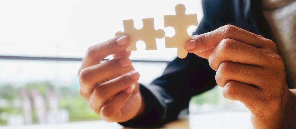 Pessoa segurando duas peças de um quebra-cabeça. Simbolizando o contrato trabalhista.