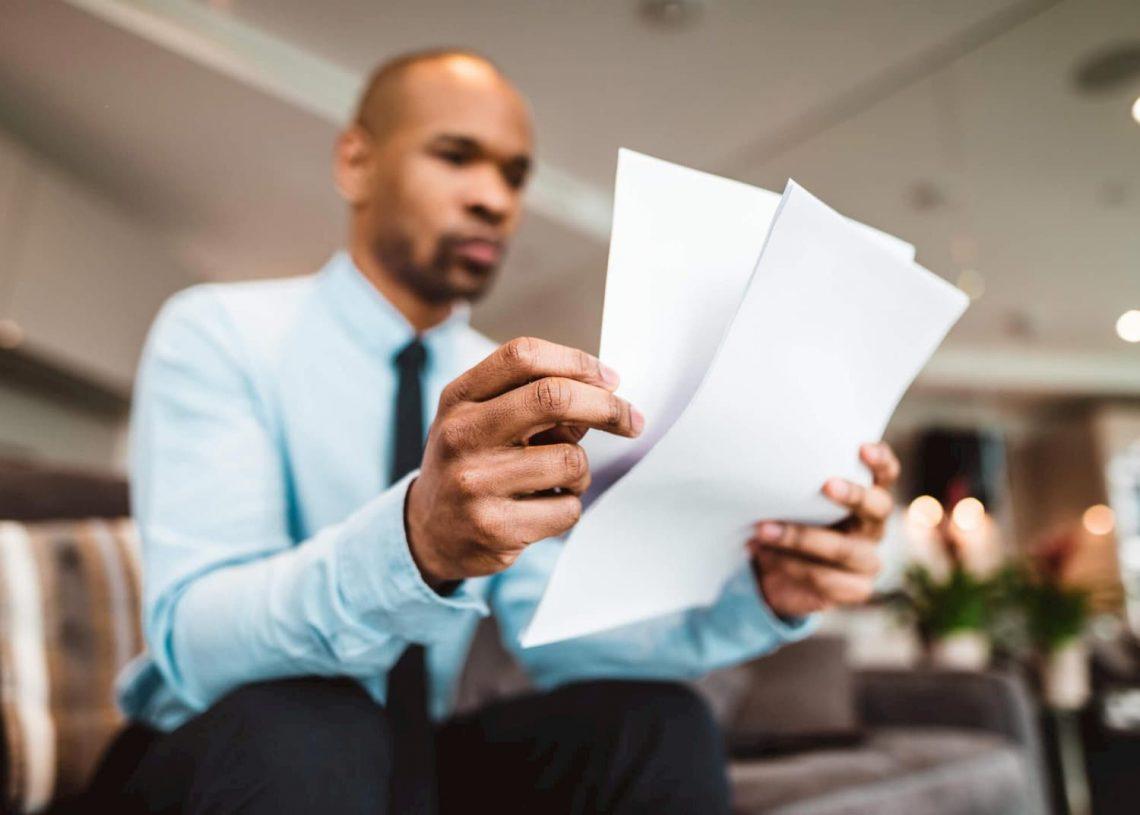 Homem negro empresário segurando alguns folhas de papel.