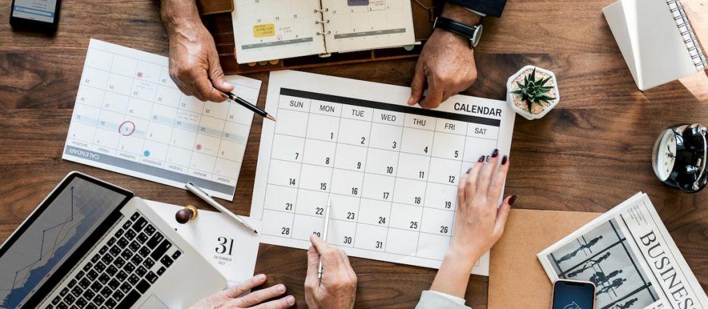 Várias pessoas apontando para um calendário.