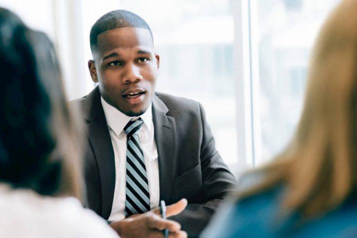 Homem negro advogado conversando com duas clientes.