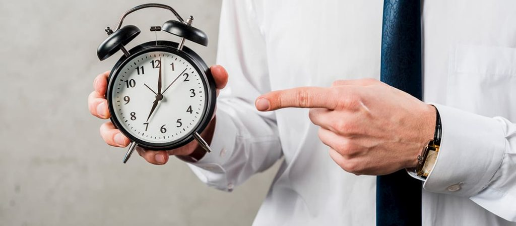 Homem segurando um relógio. Evite processos trabalhistas.