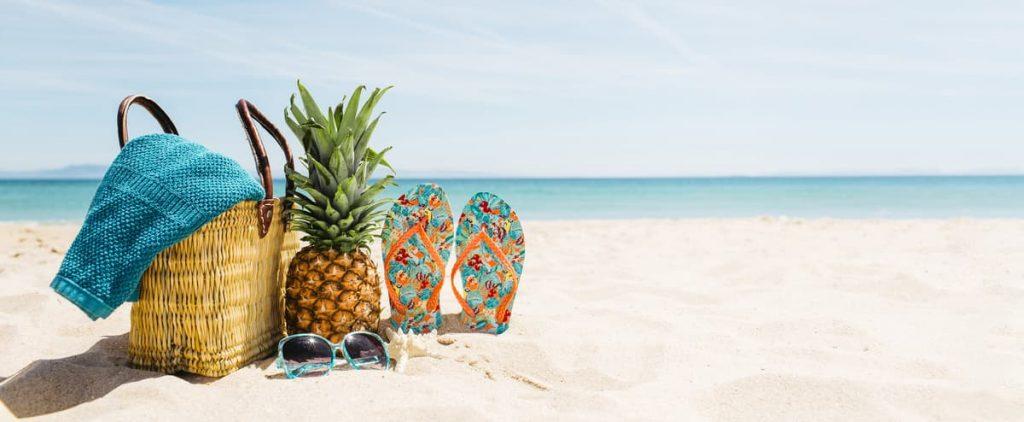 Foto de uma praia. Na areia um bolsa, chinelo e um abacaxi.