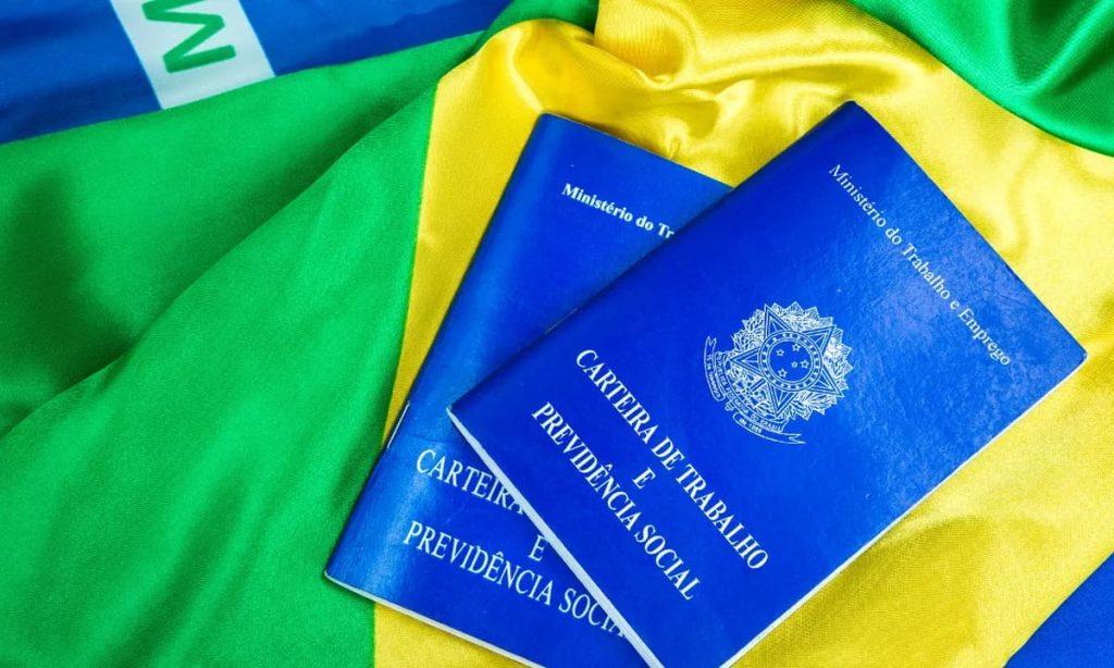Duas carteiras de trabalho em cima de uma bandeira do Brasil.