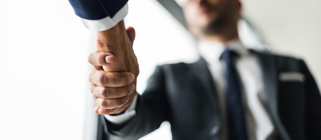 Duas pessoas apertando as mãos.