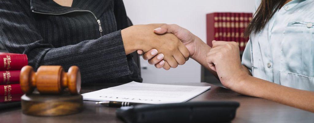 Duas mulheres fechando um negócio sobre o departamento jurídico.