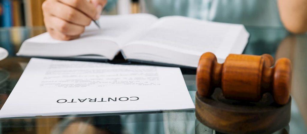 Pessoa sentada em uma mesa lendo um contrato. É importante contar com ajuda jurídica redigir um contrato.