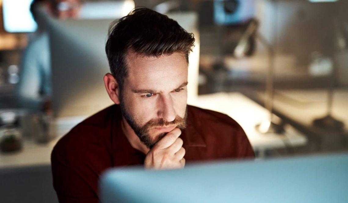 Homem sentado em frente a um notebook olhando a tela.
