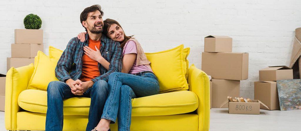 Foto de um casal sentado em seu sofá. É ter cuidado com a sociedade em família.