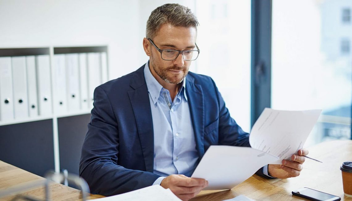 Homem segurando uma folha de papel sentado em seu escritório.