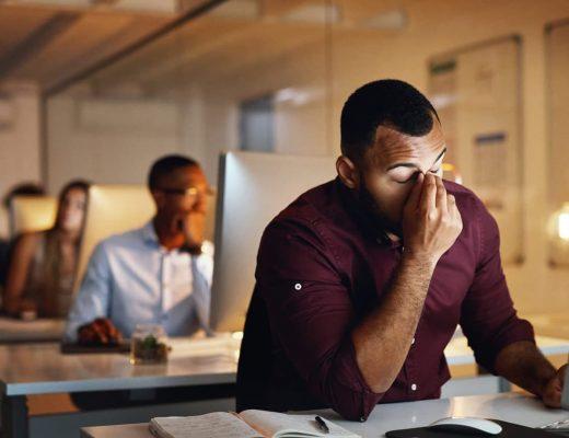 Foto de um homem negro com as mãos na cabeça sofrendo Assédio no ambiente de trabalho.
