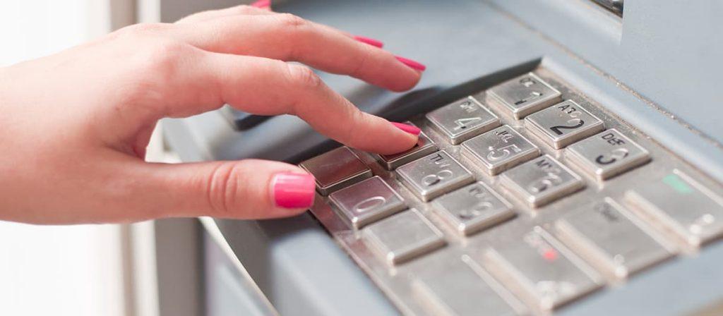 Foto de uma mulher fazendo um saque bancário.