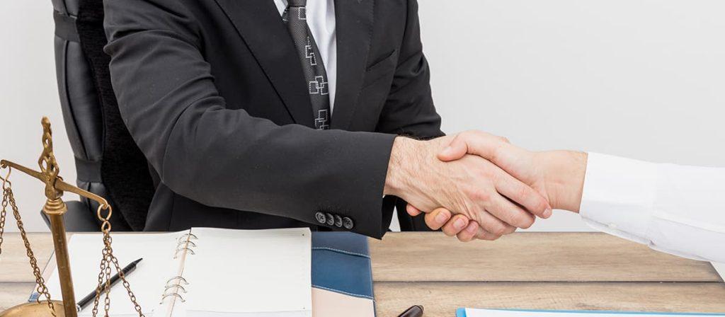 Duas pessoas apertando as mãos. Estão fechando uma parceria sobre consultoria jurídica.