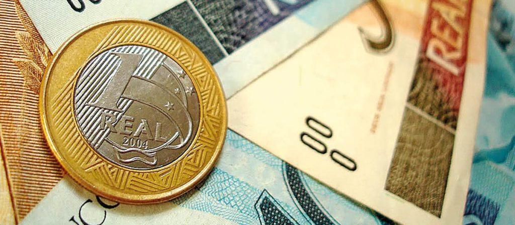 Foto de uma moeda e notas de reais.
