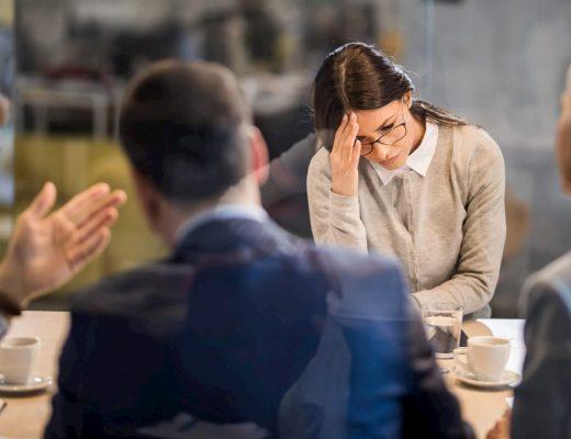 Foto de uma reunião onde uma mulher está de cabeça abaixada pensando.