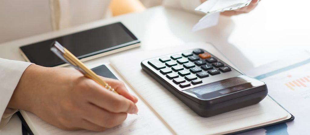Foto de uma mulher fazendo algumas contas, usando uma calculadora e um papel.