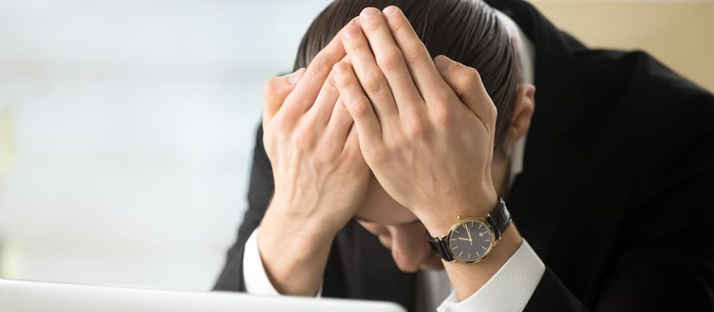 Foto de uma pessoa com as mãos na cabeça pensando sobre dívida trabalhista.