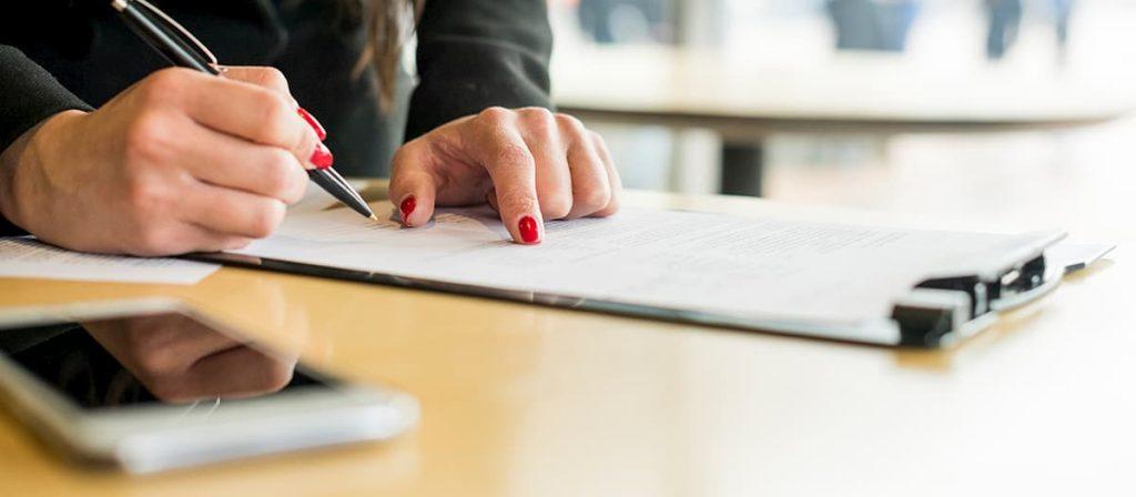 Mulher assinando um contrato de rescisão de contrato de trabalho.