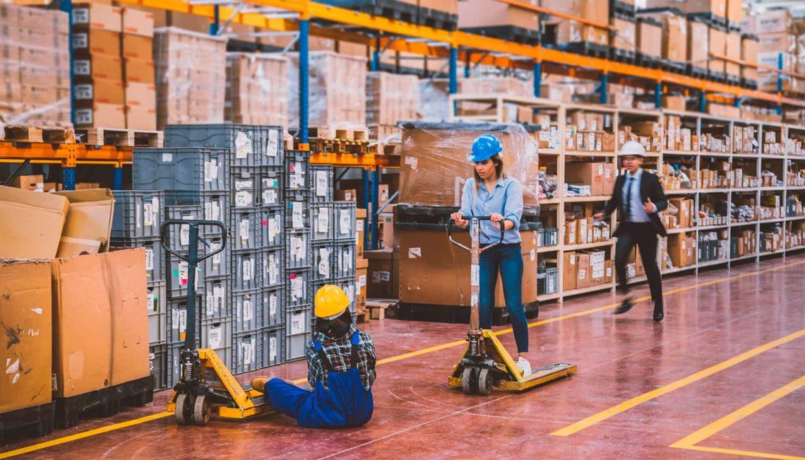 Três pessoas trabalhando no depósito de uma loja, uma está sentada e as outras em pé.