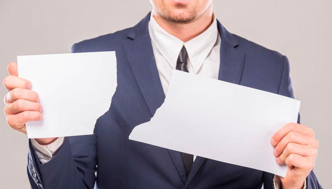 Homem rasgando um papel.