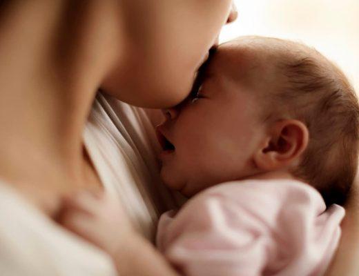 Mãe beijando seu filho recém nascido.