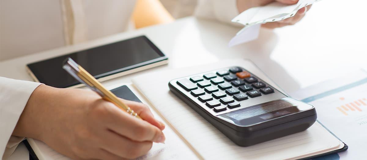 Foto de uma pessoa usando uma calculadora fazendo a consultoria tributária.