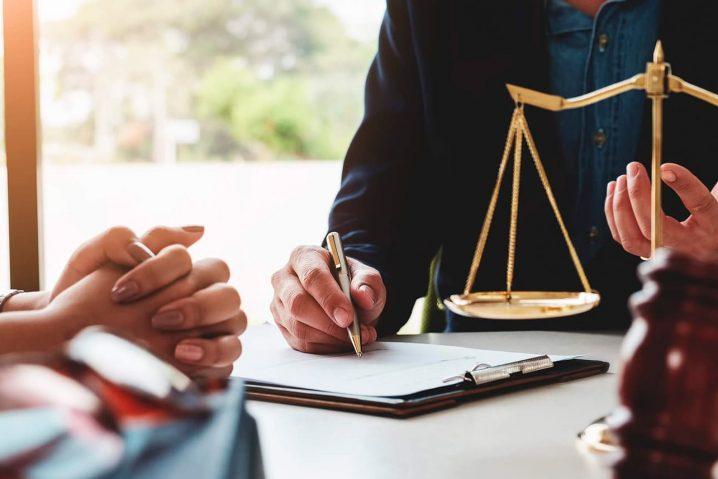 Discussão entre cliente e advogado em uma mesa jurídica.
