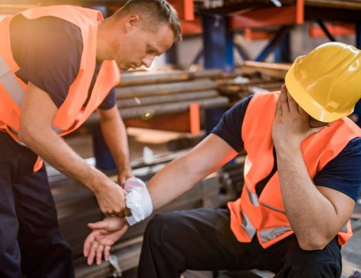 Um trabalhador auxiliando outro que está acidentado.