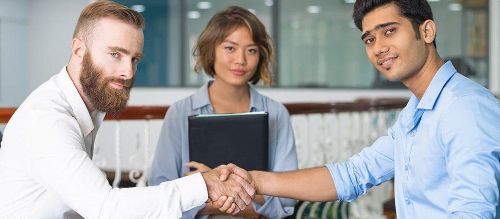 Três pessoas em uma reunião, dois homens dando um aperto de mão.