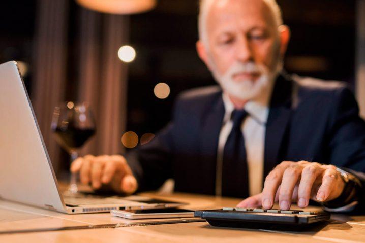 Homem usando uma calculadora e um notebook ao mesmo tempo.