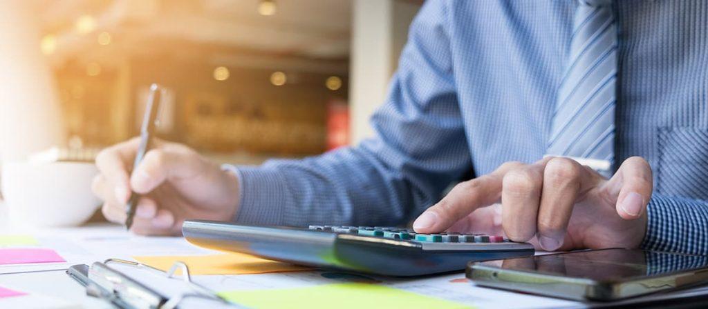 Pessoa mexendo em uma calculadora e escrevendo algo.