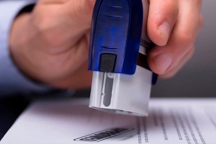Mão carimbando um documento.